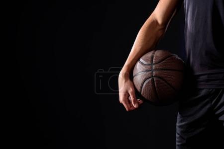 Photo pour Recadrée tir du joueur de basket-ball avec ballon isolé sur fond noir - image libre de droit