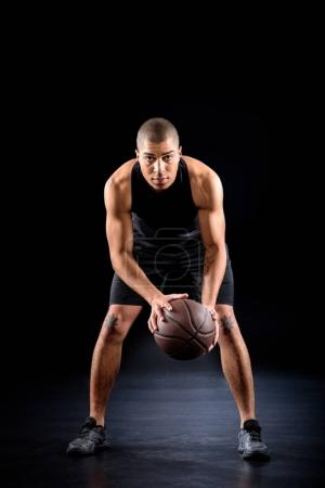 concentrated african american basketball player with ball on black