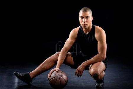 handsome african american basketball player sitting with ball on black