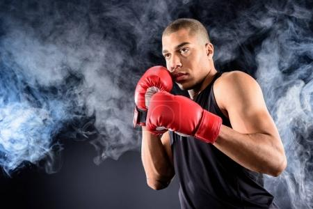 young african american boxer standing in defence position on black
