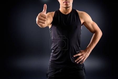 cropped shot of african american sportsman showing thumb up on black
