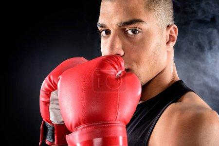 Photo pour Boxeur afro-américain regardant l'appareil photo sur fond noir - image libre de droit