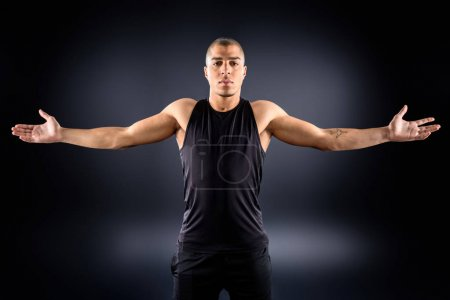 african american sportsman with outstretched arms on black