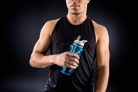 handsome african american sportsman with fitness water bottle on black