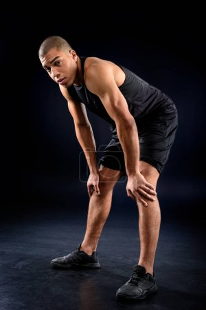 african american sportsman exhausted after workout on black