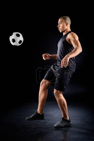 handsome african american soccer player bouncing ball on leg on black
