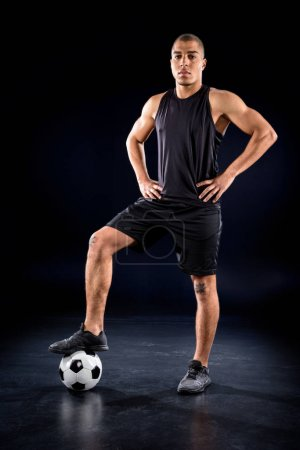 handsome african american soccer player standing with ball on black