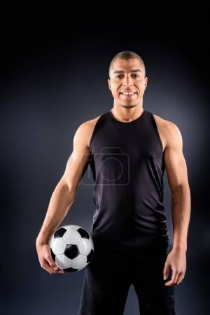 handsome african american soccer player with ball on black