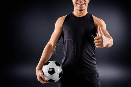 handsome african american soccer player with ball showing thumb up on black