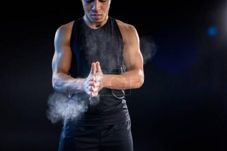 young african american sportsman clapping hands with talc on black