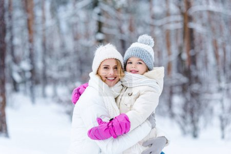 portrait of smiling daughter and mother hugging each other in winter forest