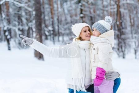 smiling mother hugging daughter and pointing away while standing in winter park