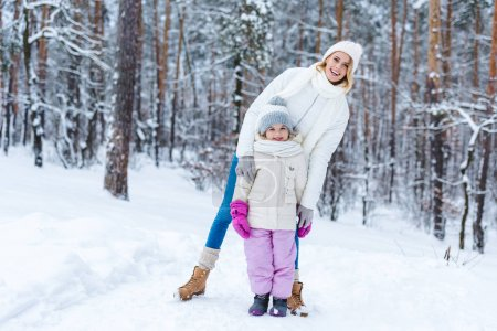 smiling mother hugging daughter while standing in winter park