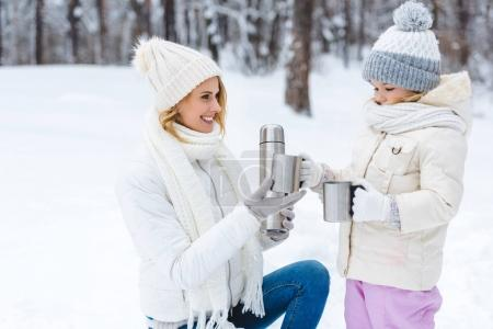 family drinking hot tea while walking in winter forest