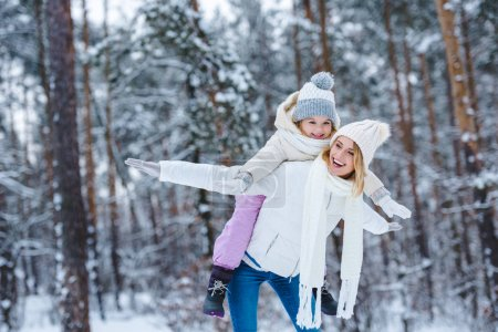 cheerful mother and little kid piggybacking together in winter park