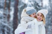 portrait of cheerful mother and little kid piggybacking together in winter park