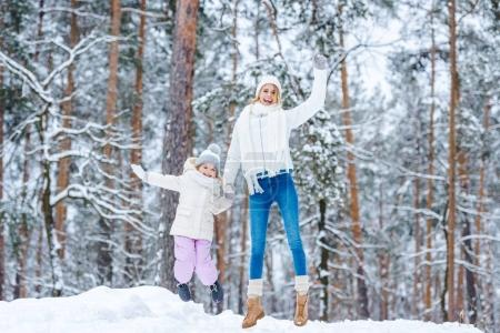 mother and little daughter having fun together in winter park