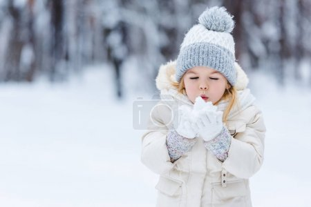 portrait of adorable kid blowing onto snow ball in hands in winter park
