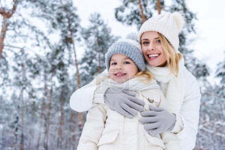portrait of smiling mother hugging daughter while standing in winter park