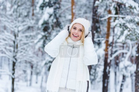 portrait of beautiful happy woman in snowy winter forest