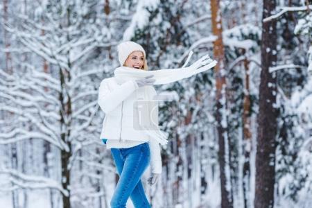 portrait of beautiful happy woman in snowy winter forest