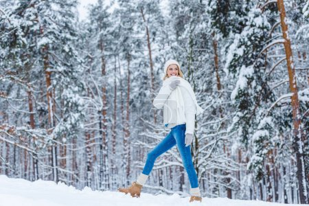 beautiful young woman walking in winter forest