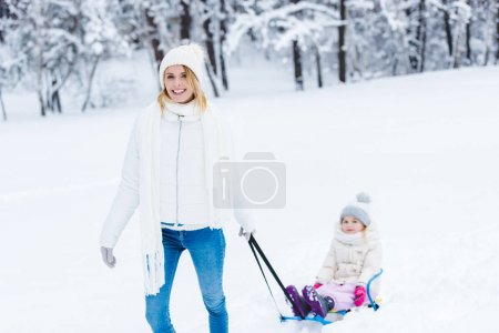 young mother and little girl sledging in winter forest together