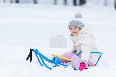 selective focus of smiling kid sitting on sledge in park