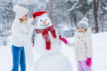 happy mother and daughter making snowman together in winter forest