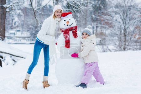 Photo for Happy mother and daughter standing near snowman together in winter forest - Royalty Free Image