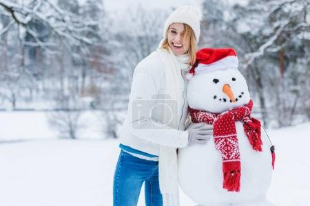 portrait of cheerful young woman standing near snowman and looking at camera