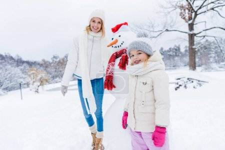 happy mother and daughter smiling at camera while standing with snowman in winter park