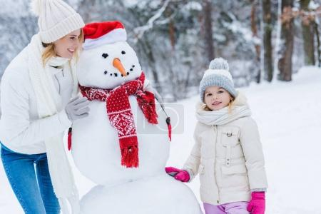 beautiful happy mother and daughter standing with snowman in winter park