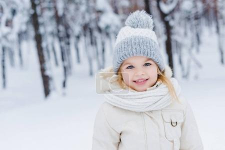 portrait of cute little child in hat and scarf smiling at camera in winter park