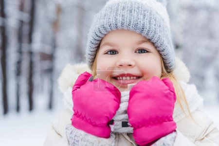 close-up portrait of cute little child in hat and mittens smiling at camera in winter park