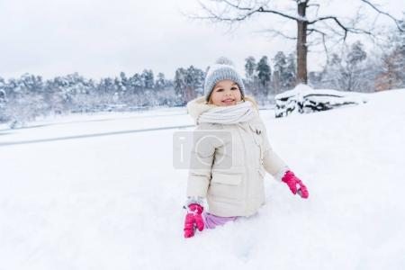 Photo for Beautiful kid smiling at camera while playing and kneeling in show - Royalty Free Image