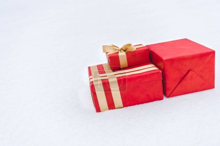 close-up view of red gift boxes wrapped with golden ribbons on snow