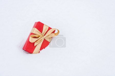 close-up view of red gift box with golden ribbon in snow