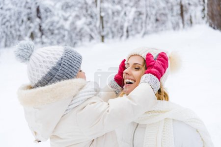 beautiful happy mother and daughter wearing hats and smiling each other in winter park