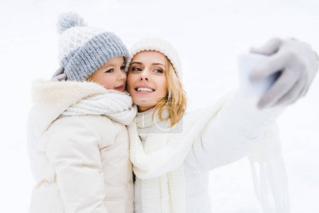 happy mother and daughter taking selfie in winter park