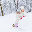 happy mother and cute little daughter making snowman together in winter park