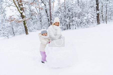 Photo pour Belle heureuse mère et fille faisant le bonhomme de neige à winter park - image libre de droit