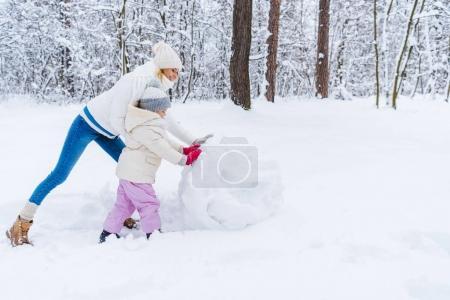 Foto de Vista lateral de la feliz madre e hija haciendo muñeco de nieve en el parque de invierno - Imagen libre de derechos
