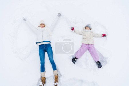 top view of happy mother and daughter making snow angels together