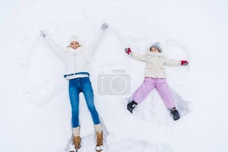 Foto de Vista superior de la feliz madre e hija haciendo Ángeles de nieve juntos - Imagen libre de derechos