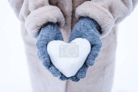 Photo pour Plan recadré de la personne tenant le symbole du cœur fait de neige - image libre de droit