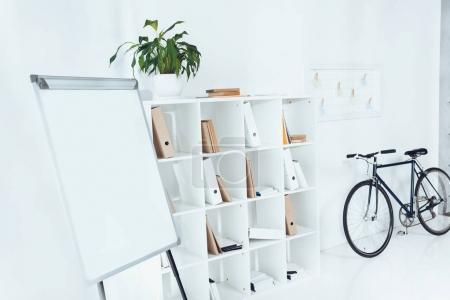 flipchart with bicycle and wooden shelves in empty office