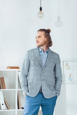 Photo pour Bel homme d'affaires debout dans le bureau et détournant les yeux - image libre de droit