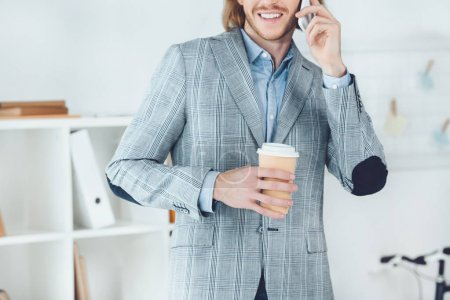 cropped image of handsome businessman talking by smartphone in office