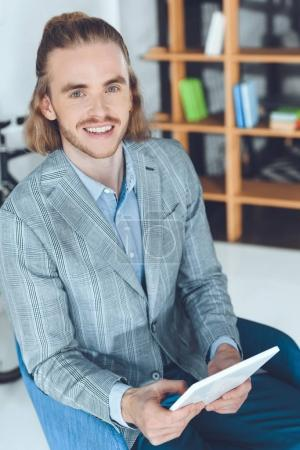 overhead view of smiling businessman sitting in chair with tablet